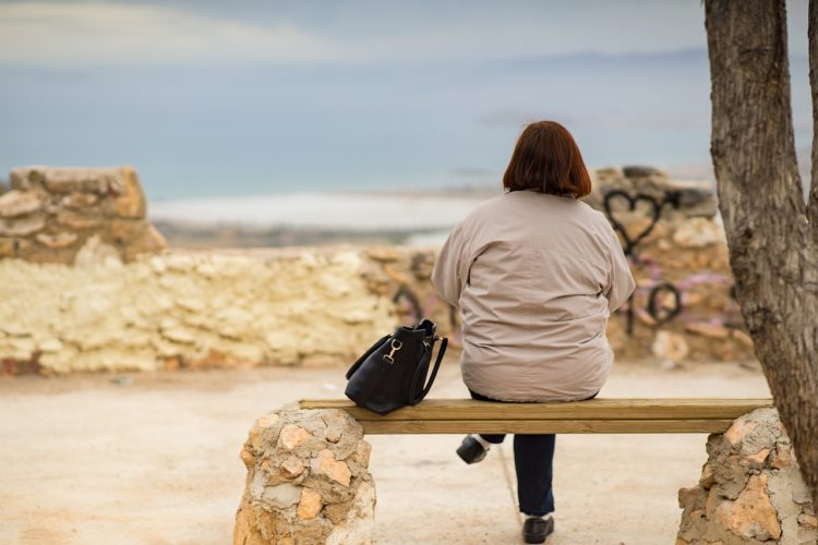 Woman sitting at a bench looking at the beach
